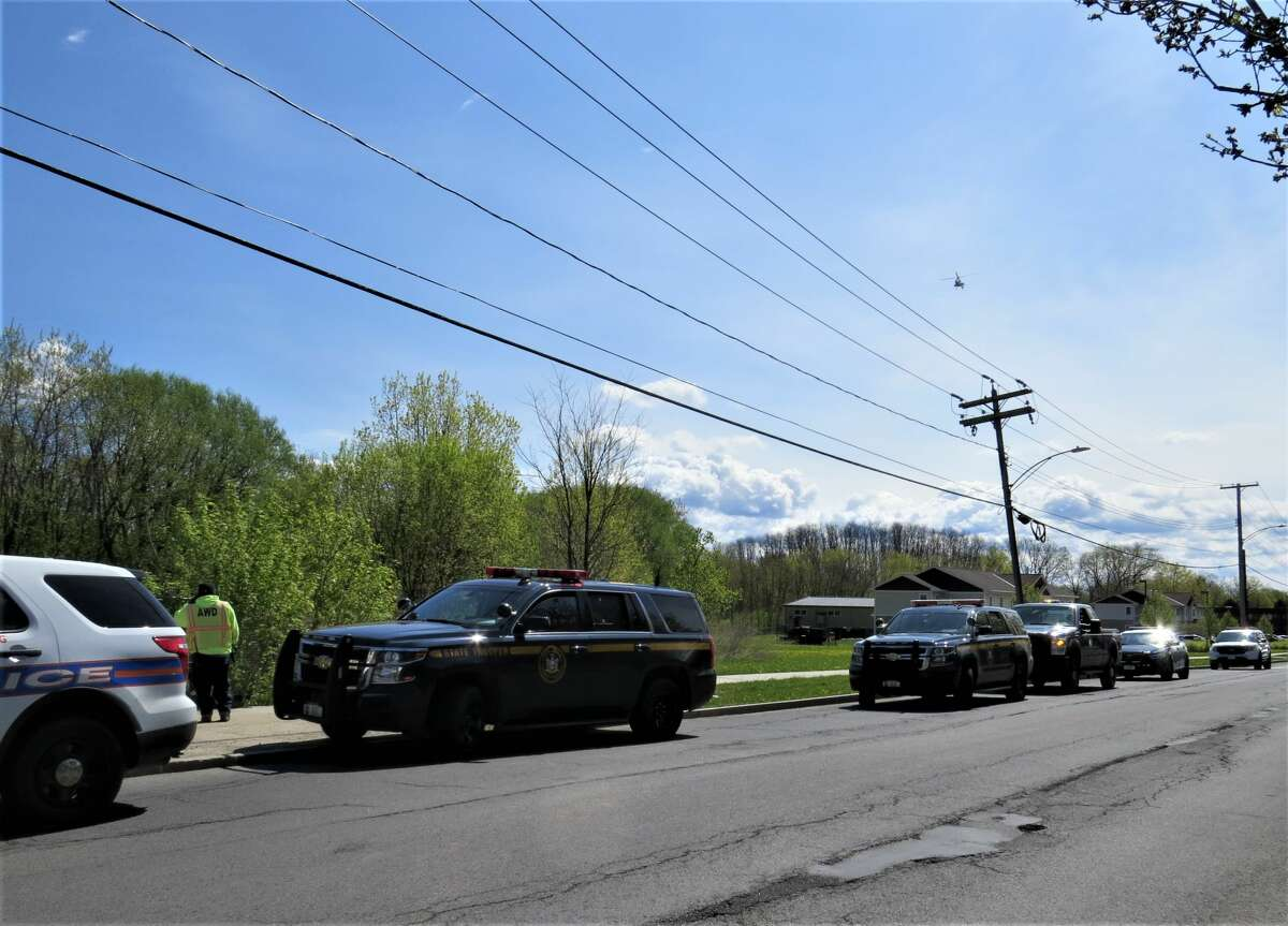 """State troopers and Albany police line the road outside Tivoli Lake Preserve in Albany as they searched for clues in the disappearance of Gustavo Oliveira, 9, who State Police said was abducted from a home early Friday in Clifton Park. Troopers said the boy was taken by Nivaldo P. Oliveira, 41, who was last seen """"traveling"""" on Tallow Wood Drive. Troopers did not describe the relationship of the boy and his alleged abductor."""