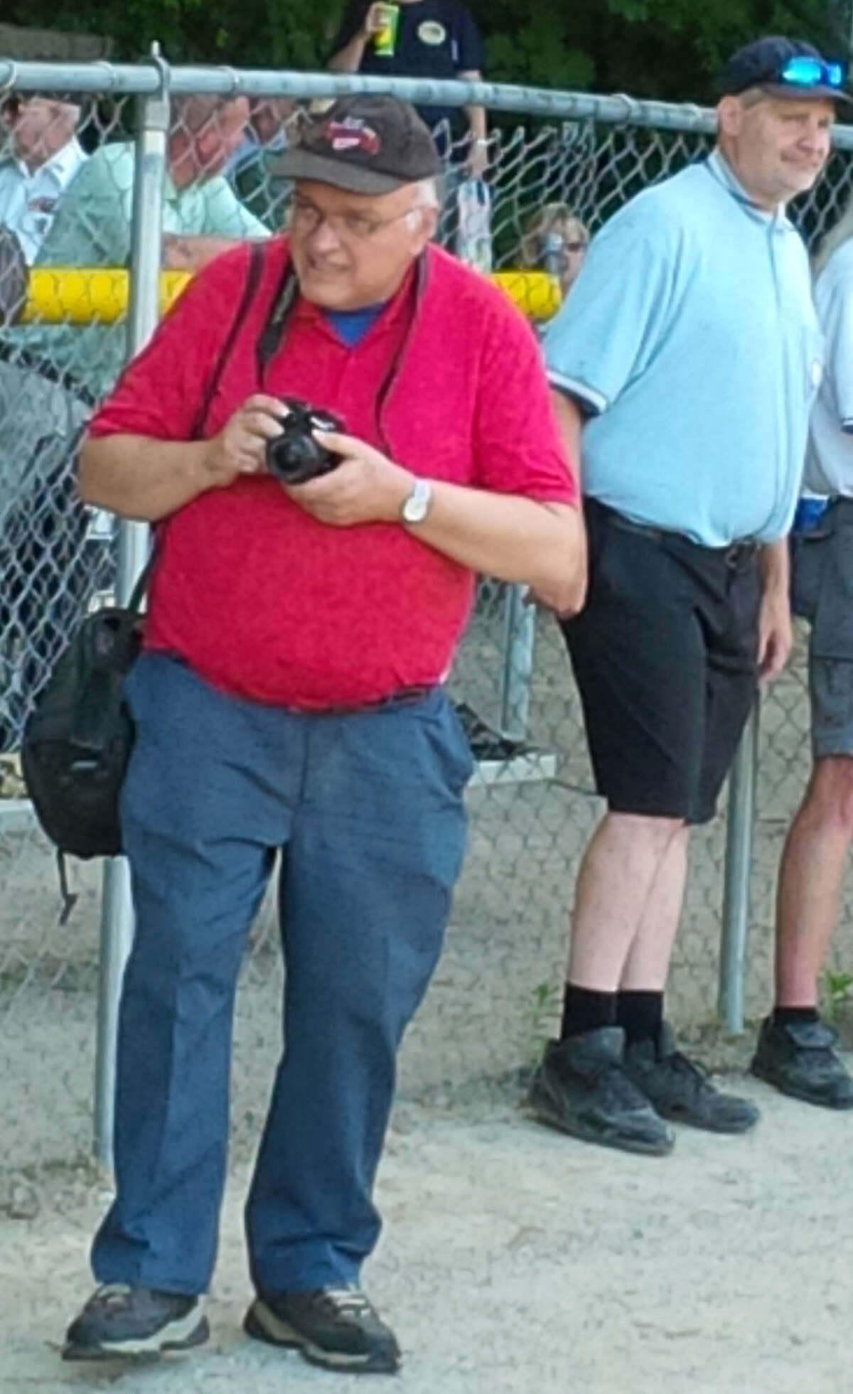 """(Left) John Raffel, sports director for the Pioneer, is pictured covering a girl's softball game. Raffel was nominated by Big Rapids High teacher Jessica Haist to be featured in the Pioneer's series, """"Heroes Unmasked,"""" which highlights those going above and behind for their communities during these challenging times. (Courtesy photo)"""