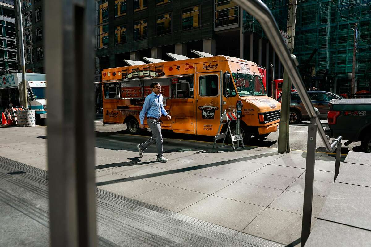 A man walks past the JapaCurry food truck during lunchtime in SOMA on Wednesday, March 11, 2020 in San Francisco, California. There are usually long lines for JapaCurry and other food trucks in the area. They said that the coronavirus which has forced employees to work from home has significantly impacted their sales.