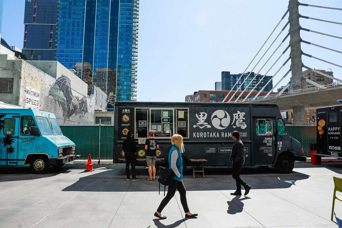 People walk past food trucks for lunch outside the Transbay Terminal on Wednesday, March 11, 2020 in San Francisco, California. Despite dozens of people coming out for lunch, it was much quieter than normal due to many people working from home because of the coronavirus.