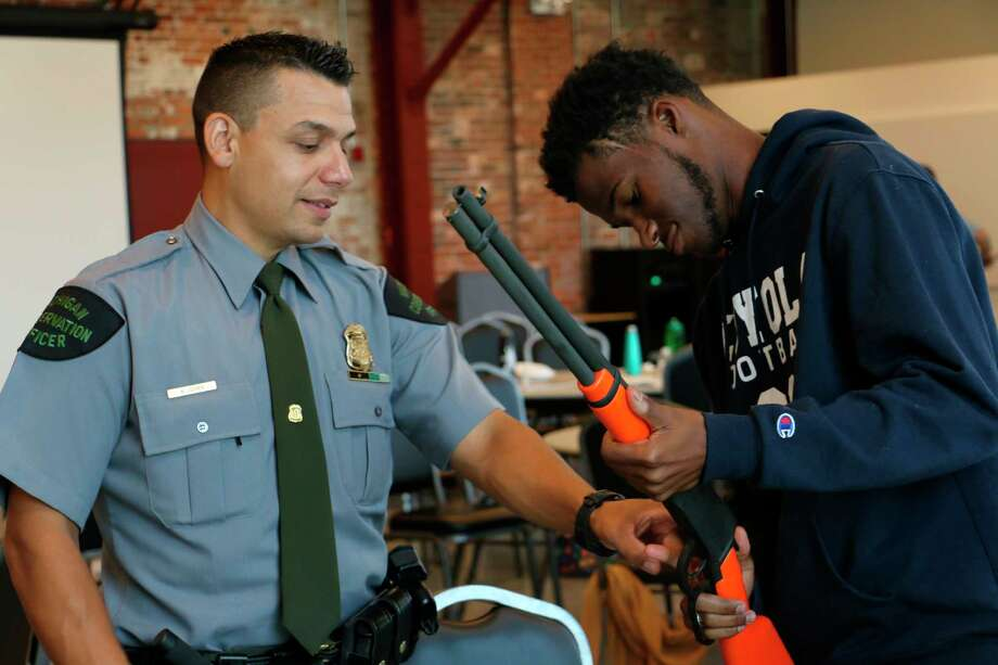 Michigan DNR Conservation Officer Keven Luther works with a young man during an August 2019 hunter education safety course. (Courtesy photo)