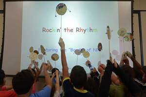 Campers hold up their spin drums during Music Camp at the Norwalk Public Library on Aug. 22, 2018. The week-long camp centered on music, the summer reading theme.