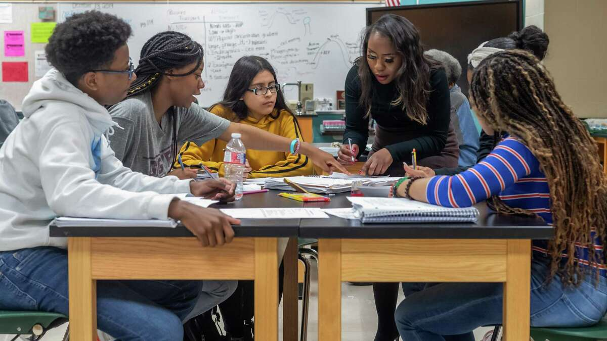 A teacher works with some of her ninth-grade students on a science project in 2019. Things won't be back to normal until classrooms look like this again, and the pandemic demands support for public education as it evolves through this crisis.