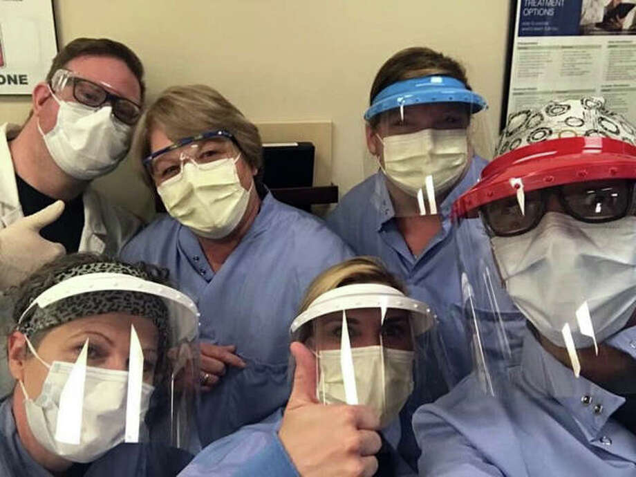 Shawna McMichael, front row center, and other members of her team from the home dialysis program at Washington University pose while wearing their personal protective equipment. Photo: For The Intelligencer