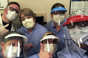 Shawna McMichael, front row center, and other members of her team from the home dialysis program at Washington University pose while wearing their personal protective equipment.