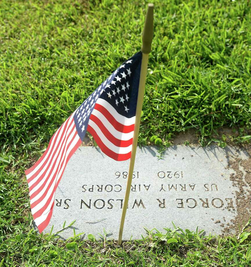 A flag is set at a veteran's marker as scouts, American Legion members and others prepare veterans' gravesites for Memorial Day at Forest Lawn Memorial Park in 2019. Winsted's VFW invites members of the community to join them May 24 to place flags on veterans' graves in the town's cemeteries. Photo: Kim Brent / The Enterprise / BEN
