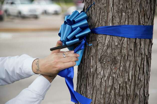 Mike Cummings ties a blue ribbon around one of the trees that surround Memorial City Mall on Friday, May 8, 2020 in Houston. Memorial City will Shine Blue, with blue ribbons and the buildings, bridges and garages lit in blue, in recognition of National Nurses Week and National Hospital Week and to honor those healthcare heroes fighting on the frontline against COVID-19. Photo: Brett Coomer, Staff Photographer / © 2020 Houston Chronicle