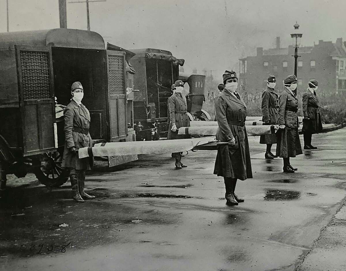 A photo provided by the Library of Congress, women in face masks hold stretchers near ambulances during the Spanish Flu pandemic in St. Louis, Mo. in October 1918. Researchers found valuable lessons in the city's response. The concept of social distancing is now intimately familiar to almost everyone but as it first made its way through the federal bureaucracy in 2006 and 2007, it was viewed as impractical, unnecessary and politically infeasible.