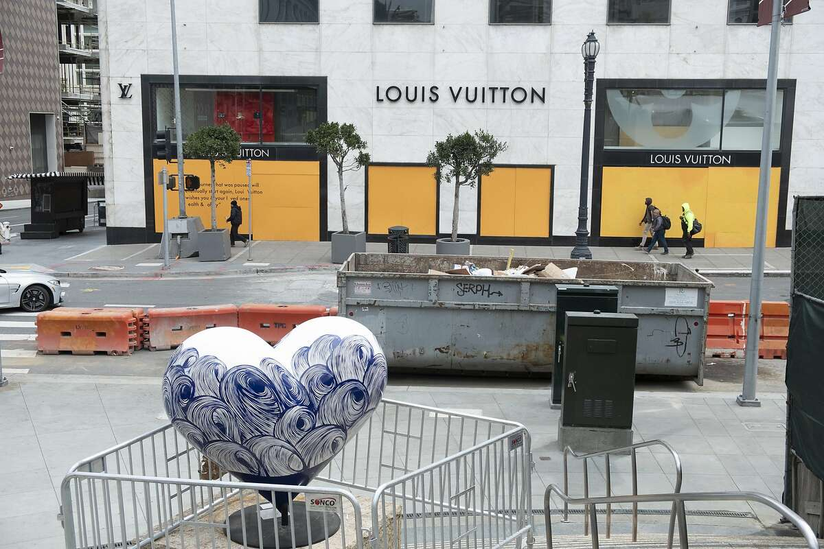 In this April 17, 2020, photo, people walk past a boarded up storefront at Union Square in San Francisco. San Francisco's mayor is under growing pressure to house all of the city's 8,000 homeless residents in hotel rooms left empty by the coronavirus pandemic. (AP Photo/Eric Risberg)