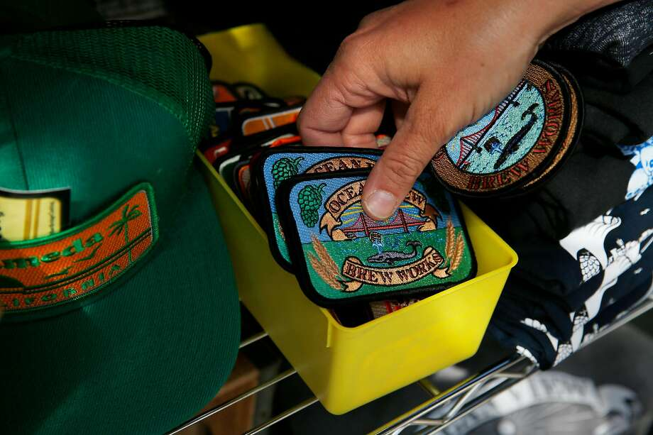 Vonnie Davidson adds Ocean View Brew Works patches to items for sale at her brewery turned store in Albany. Photo: Lea Suzuki / The Chronicle