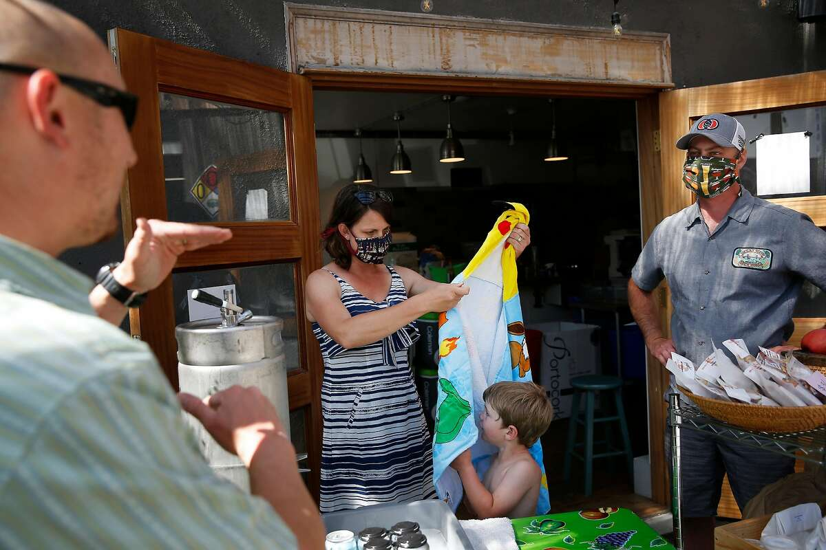 Scott Davidson (right), co-owner Ocean View Brew Works, Vonnie Davidson (second from left), co-owner Ocean View Brew Works, talk with local farmer market vendor, Steve Yee (left) as Vonnie Davidson assists son Nico (second from right) with a towel robe as they work at their store at Ocean View Brew Works on Wednesday, May 6, 2020 in Albany, Calif.