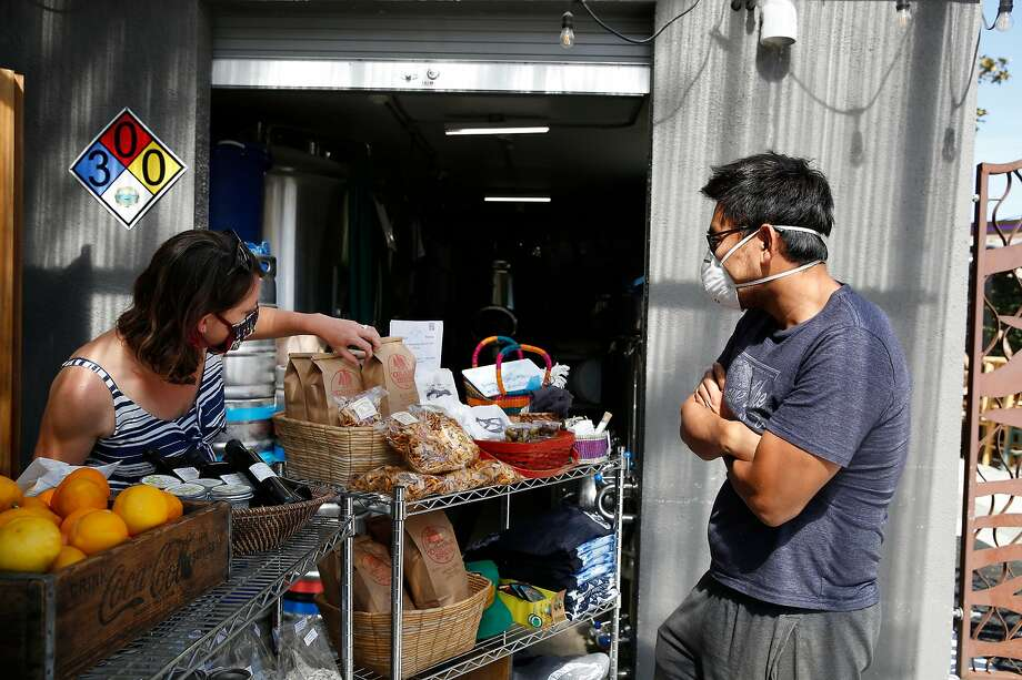 Vonnie Davidson (l to r), co-owner Ocean View Brew Works, assists customer Eric Xu, of El Cerrito, as he shops at the store at Ocean View Brew Works on Wednesday, May 6, 2020 in Albany, Calif. Photo: Lea Suzuki / The Chronicle
