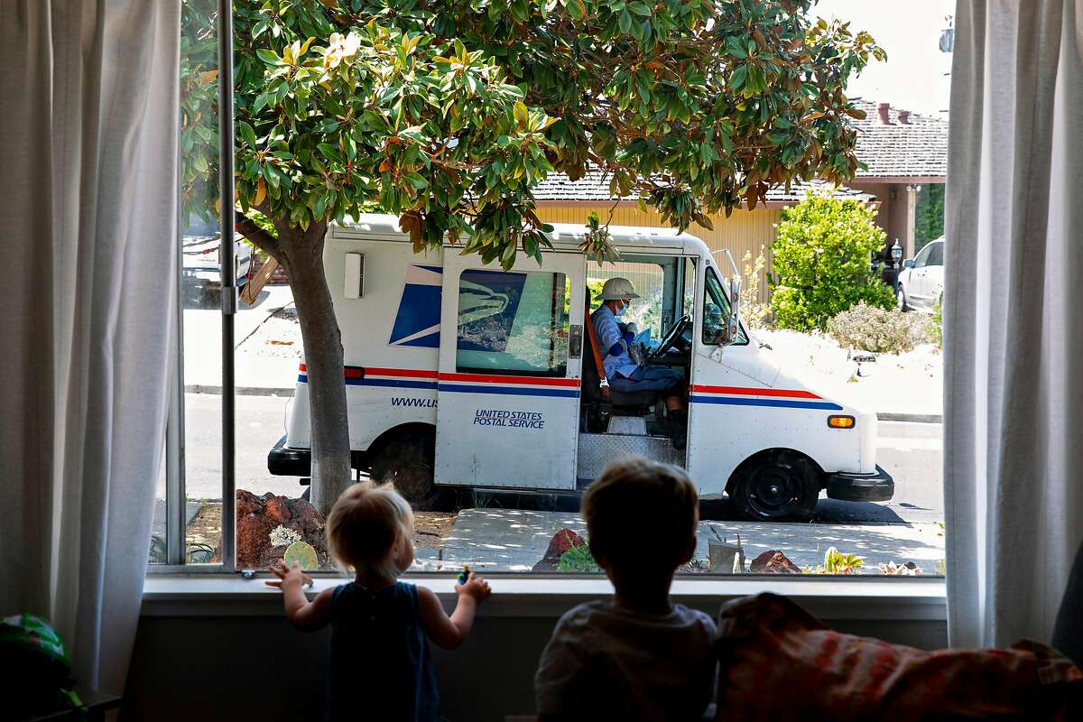 Leila Havenar-Daughton, 1, and Liam Havenar-Daughton, 3, watch through the window as the mail man completes his route while parked in front of their home in El Sobrante, Calif. Thursday, May 7, 2020. Despite federal and state funding, hundreds of childcare facilities may shut down due to the Coronavirus pandemic, leaving parents with nowhere to leave their kids when the economy reopens and they want to return to work. The Havenar-Daughtons pay $1,900 a month for childcare they can't use during the shelter in place period, fearing that otherwise they might lose the preschool and nanny who watches their children.