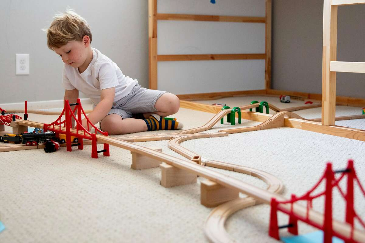Liam Havenar-Daughton, 3, plays with a toy train set in the bedroom of his home in El Sobrante, Calif. Thursday, May 7, 2020. Despite federal and state funding, hundreds of childcare facilities may shut down due to the Coronavirus pandemic, leaving parents with nowhere to leave their kids when the economy reopens and they want to return to work. The Havenar-Daughtons pay $1,900 a month for childcare they can't use during the shelter in place period, fearing that otherwise they might lose the preschool and nanny who watches their children.