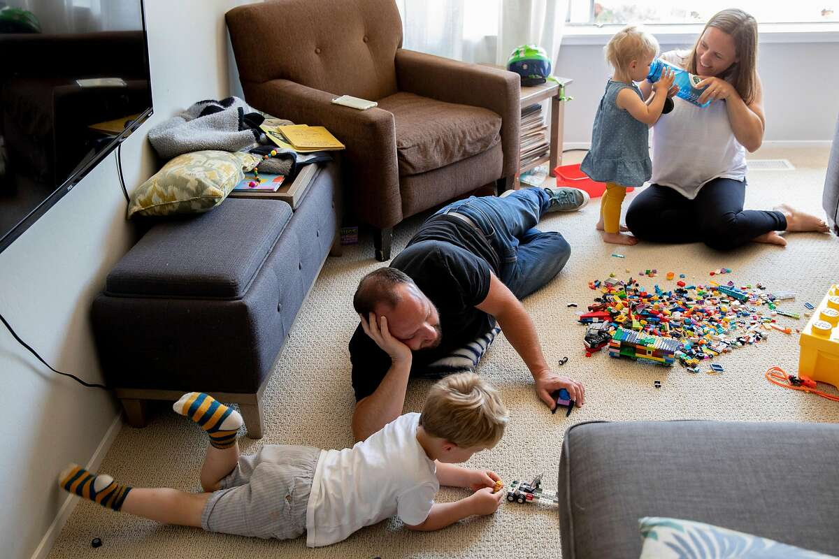 Brendan and Alice Havenar-Daughton help their children Liam, 3, and Leila, 1, set up Lego toys in the living room of their home in El Sobrante, Calif. Thursday, May 7, 2020. Despite federal and state funding, hundreds of childcare facilities may shut down due to the Coronavirus pandemic, leaving parents with nowhere to leave their kids when the economy reopens and they want to return to work. The Havenar-Daughtons pay $1,900 a month for childcare they can't use during the shelter in place period, fearing that otherwise they might lose the preschool and nanny who watches their children.