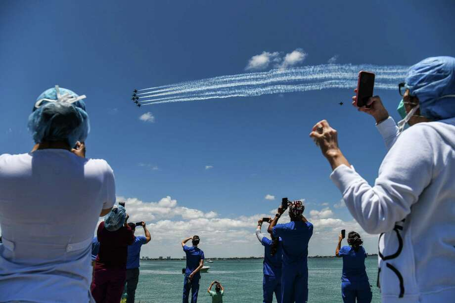 Health care workers gather by the bay to watch the U.S. Navy Blue Angels and U.S. Air Force Thunderbirds fly over Mount Sinai Medical Center in Miami on Friday. The Thunderbirds will fly over San Antonio and Austin on Tuesday. (Photo by CHANDAN KHANNA / AFP) (Photo by CHANDAN KHANNA/AFP via Getty Images) Photo: CHANDAN KHANNA /AFP Via Getty Images / AFP or licensors