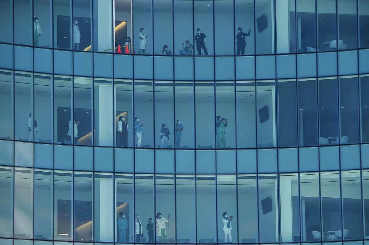 Health care workers watch from inside the building the U.S. Navy Blue Angels and U.S. Air Force Thunderbirds fly over the Mount Sinai Medical Center in Miami on Friday. The Thunderbirds will fly over San Antonio and Austin on Tuesday. (Photo by CHANDAN KHANNA / AFP) (Photo by CHANDAN KHANNA/AFP via Getty Images)