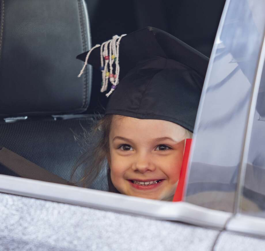 Midland College Pre-K Academy graduate Makynlee Lavender smiles for a picture in her graduation cap 05/08/2020 as parents drive through the parking lot to receive their diploma as the first class to graduate from the Academy. Tim Fischer/Reporter-Telegram Photo: Tim Fischer/Midland Reporter-Telegram