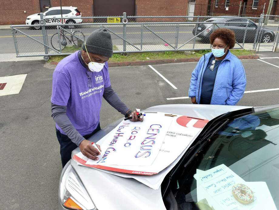 Addie Kimbrough (right) watches Keith Lawrence (left) finish a sign for the Party-On-Wheels to publicize the 2020 Census in the parking lot of the Second Star of Jacob Church in New Haven where the caravan began on May 8, 2020. Photo: Arnold Gold / Hearst Connecticut Media / New Haven Register