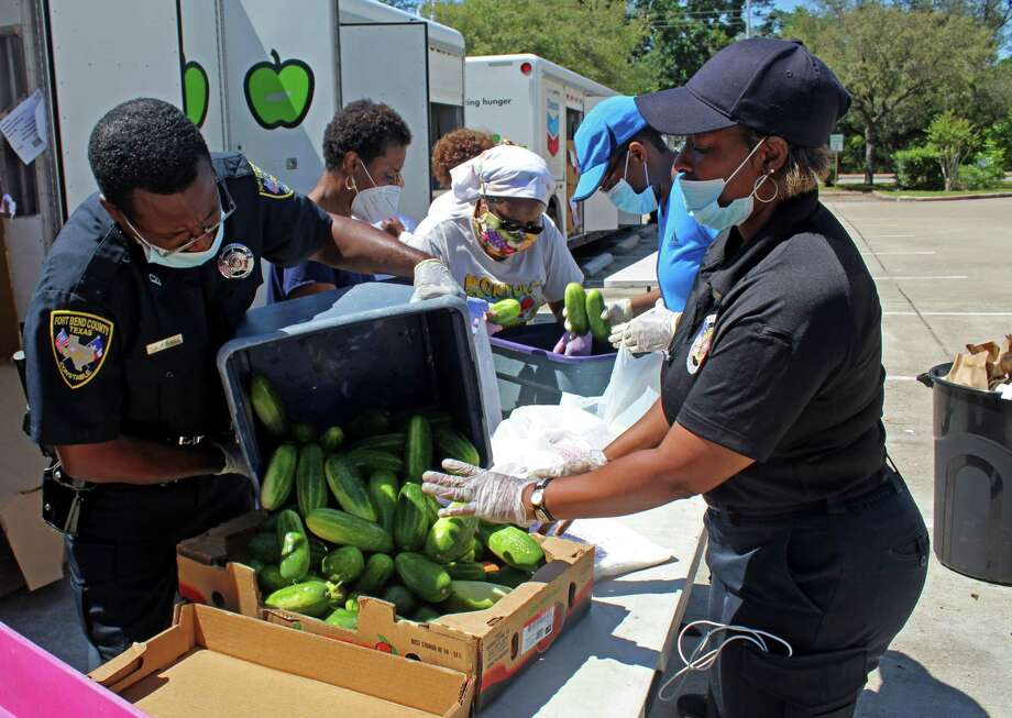 Fort Bend County Precinct 2 Constable Deputies and volunteers work at a distribution food drive in Missouri City on Friday, May 1. Photo: Kristi Nix