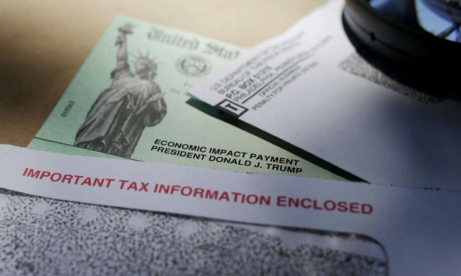 In this April 23, 2020, file photo, President Donald Trump's name is seen on a stimulus check issued by the IRS to help combat the adverse economic effects of the COVID-19 outbreak, in San Antonio. President Donald Trump, Treasury Secretary Steven Mnuchin and now the IRS are urging people who received coronavirus relief payments for a deceased taxpayer to return the money to the government. But legal experts say there is no law requiring people do that. (AP Photo/Eric Gay, File) Photo: Eric Gay / Associated Press