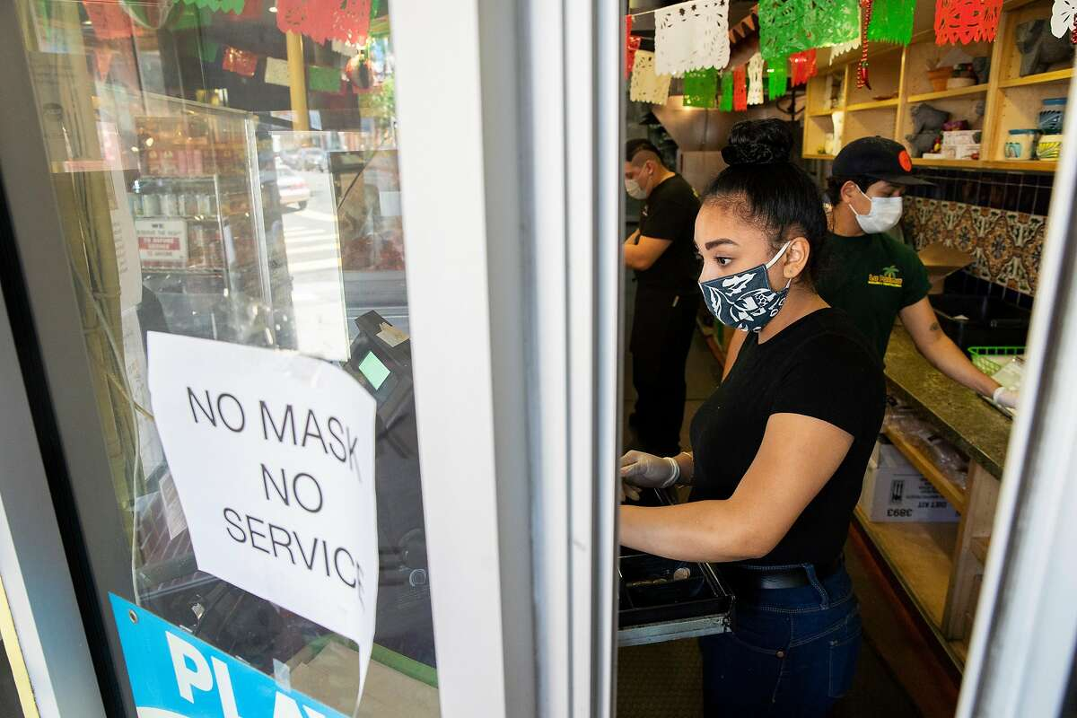 Araceli Flores rings up a customer at Araceli Flores along 24th Street on Thursday, May 7, 2020, in San Francisco, Calif. Amid the coronavirus pandemic, the business refuses to serve anyone without a mask.