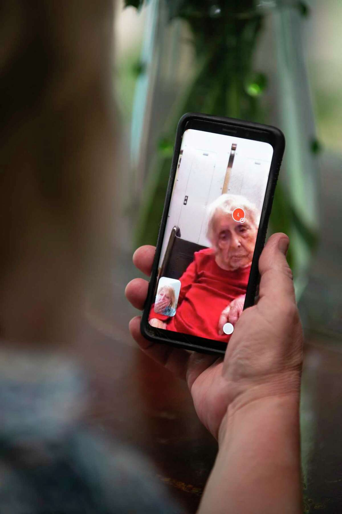 Susan Russell speaks with her mother on a video call Friday in Houston. Russell has been trying to find ways to stay connected with her mom since coronavirus precautions started preventing her from visiting her in person at the Houston memory care facility where she lives.