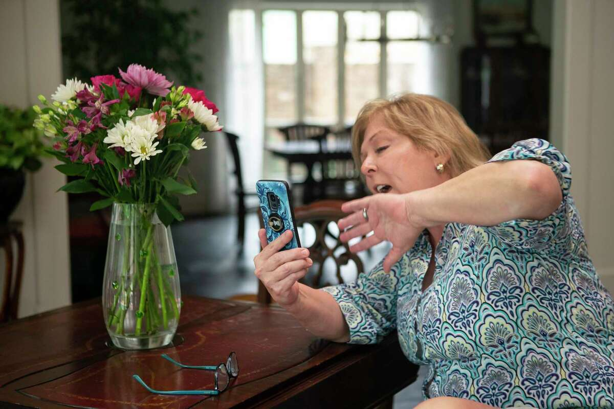 Susan Russell waves at her mother as she speaks with her on a video call. Russell has been trying to find ways to stay connected with her mom since coronavirus precautions started preventing her from visiting her in person at the Houston memory care facility where she lives.