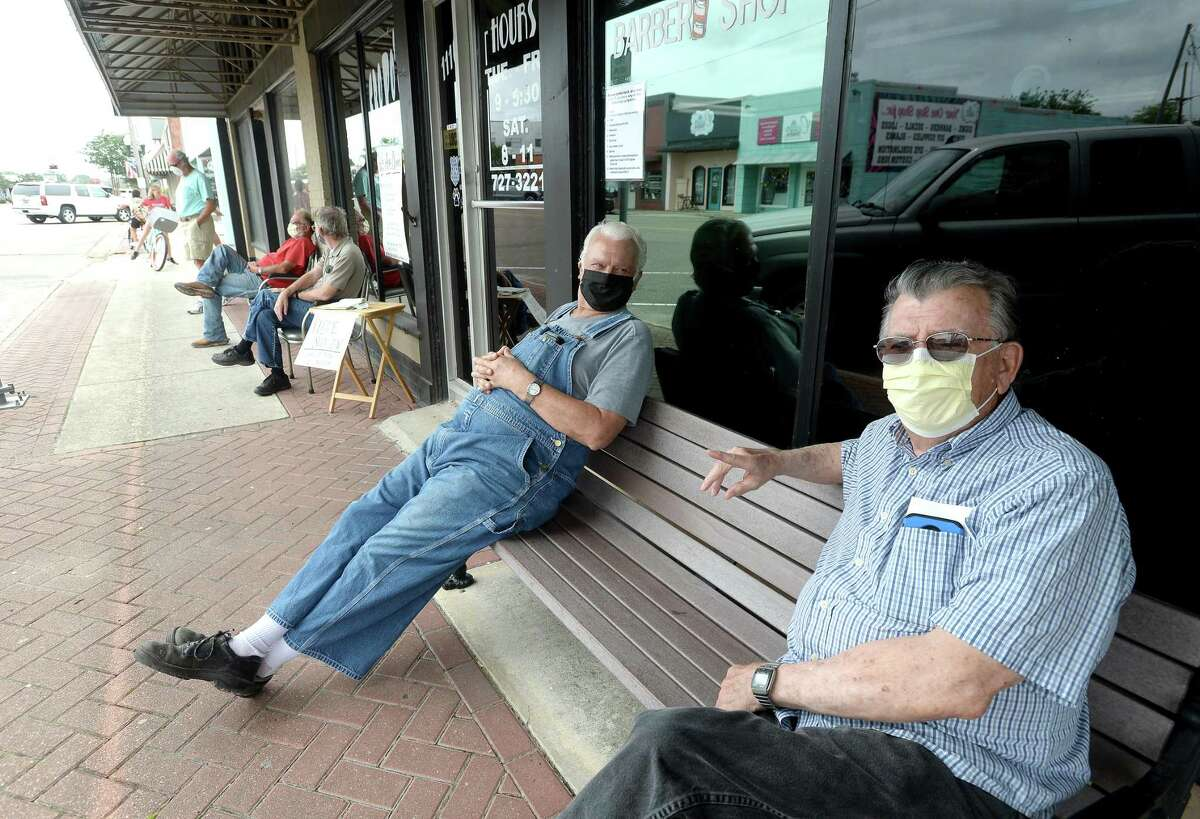 James Davis (left) talks with Wally Werner as they sit outside Cropo's Barber Shop in Nederland and await their turn being called inside on the first day of reopening for salons, barber shops, and nail salons Friday. Photo taken Friday, May 8, 2020 Kim Brent/The Enterprise