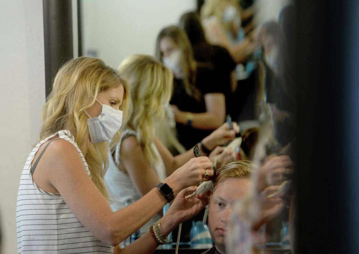 Owner Leah Laing gives a cut to her first client in six weeks, Bailey Braneff, as employee Alyssa Savell does a coloring job for Caity Cossey at The Loft on the first day of reopening for salons, barber shops, and nail salons Friday. Photo taken Friday, May 8, 2020 Kim Brent/The Enterprise