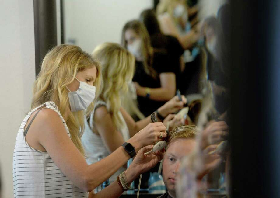 Owner Leah Laing gives a cut to her first client in six weeks, Bailey Braneff, as employee Alyssa Savell does a coloring job for Caity Cossey at The Loft on the first day of reopening for salons, barber shops, and nail salons Friday. Photo taken Friday, May 8, 2020 Kim Brent/The Enterprise Photo: Kim Brent / The Enterprise / BEN
