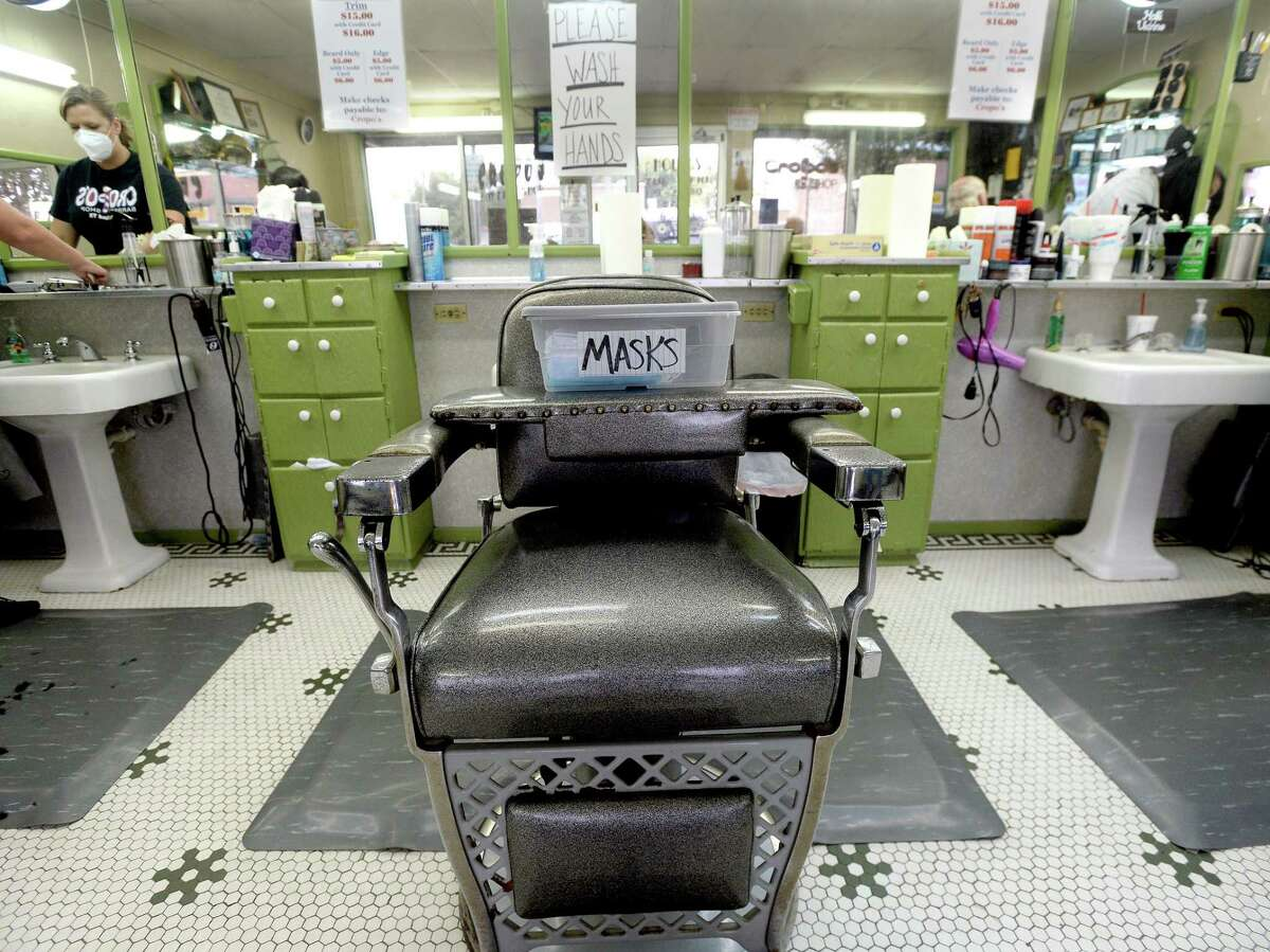 A carton of fresh masks sits onn a middle chair at Cropo's Barber Shop in Nederland on the first day of reopening for salons, barber shops, and nail salons Friday. Photo taken Friday, May 8, 2020 Kim Brent/The Enterprise