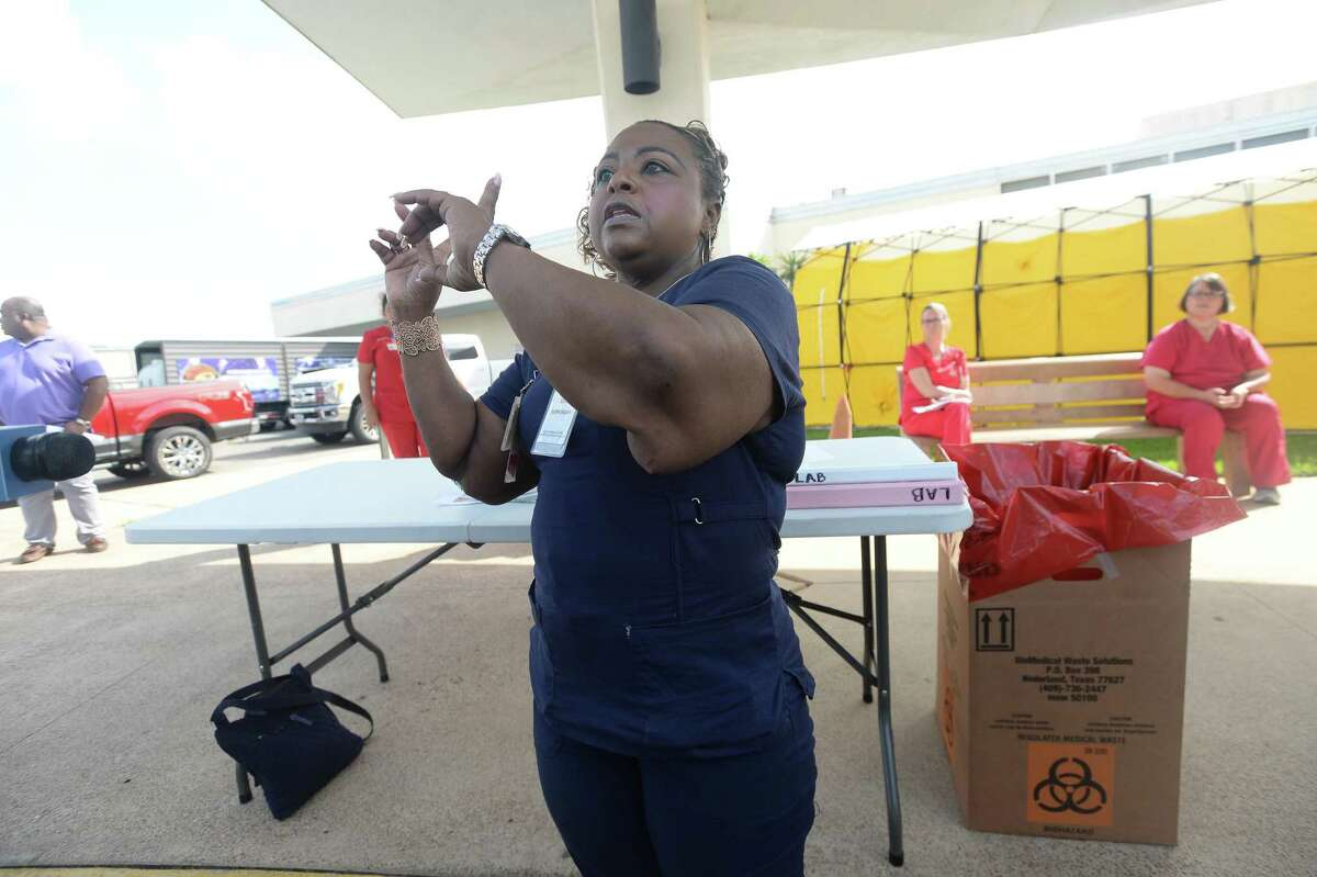Nurse LaTasha Mayon describes the procedure for testing that will take place at the drive-thru testing unit for COVID-19 at Jack Brooks Regional Airport Monday, which will open Tuesday morning. They expect to test roughly 25 people per day and already have a full testing schedule for their opening day. The testing center will service residents throughout several Southeast Texas counties. Photo taken Monday, March 23, 2020 Kim Brent/The Enterprise