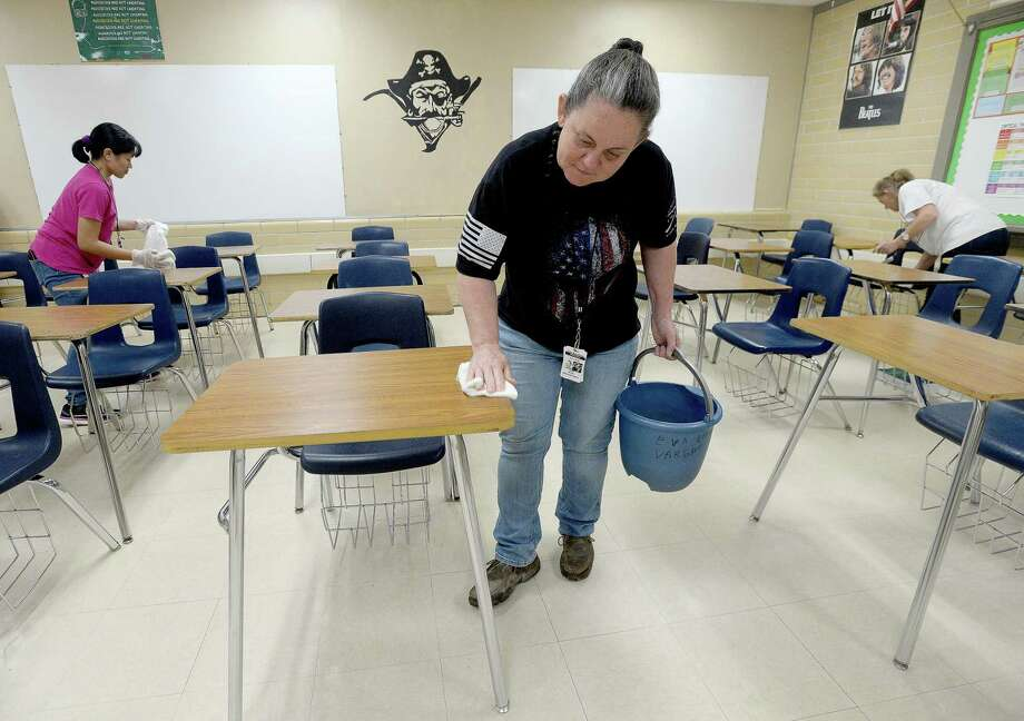 Tammy Hester, (center) head custodian for Vidor ISD, joins Marye Jane Cuntapay (left) and Tanya Crum in a classroom as they continue deep cleaning at Vidor High School Monday. Custodial staff, several of whom have volunteered their time off over spring break to complete cleaning projects at campuses throughout the district, will continue cleaning to get rid of any potential viruses and in preparation for school reconvening after the break is over next week. Photo taken Monday, March 16, 2020 Kim Brent/The Enterprise Photo: Kim Brent / The Enterprise / BEN