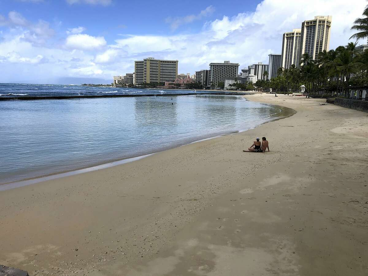 A couple sits on an empty section of Waikiki Beach in Honolulu. Hawaii law enforcement authorities are cracking down on rogue tourists who are visiting beaches, jetskiing, shopping and generally flouting strict requirements that they quarantine for 14 days after arriving. (AP Photo/Caleb Jones, File)