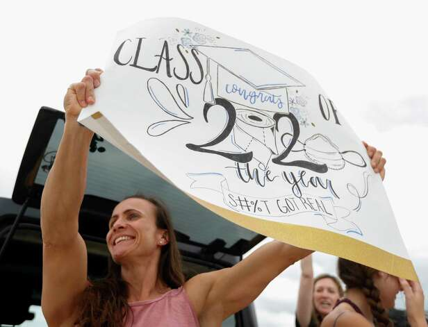 Monica Hughes, left, holds a sign for seniors as the graduating class at Lake Creek High School picked up graduating appeal and yard signs, Friday, May 8, 2020, in Montgomery. Photo: Jason Fochtman, Staff Photographer / 2020 © Houston Chronicle