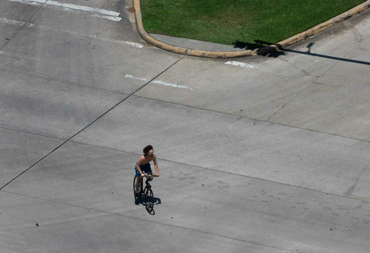 A bicyclist pedals through the intersection of Cambridge and South MacGregor on May 6, 2020, in Houston.
