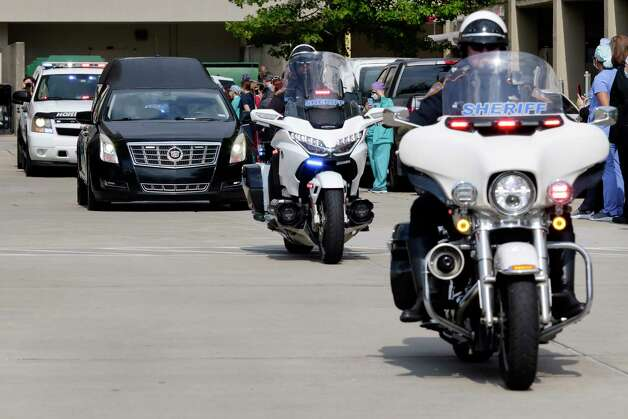The procession of law enforcement vehicles escort the hearse carrying Harris County Sheriff's Office Sgt. Raymond Scholwinski Friday, May 8, 2020, as it leaves Memorial Hermann hospital in The Woodlands, TX en route back to Houston. Scholwinski, age 70,  died of COVID-19 after a weeks long battle with the virus at the hospital. Photo: Michael Wyke, Contributor / © 2020 Houston Chronicle