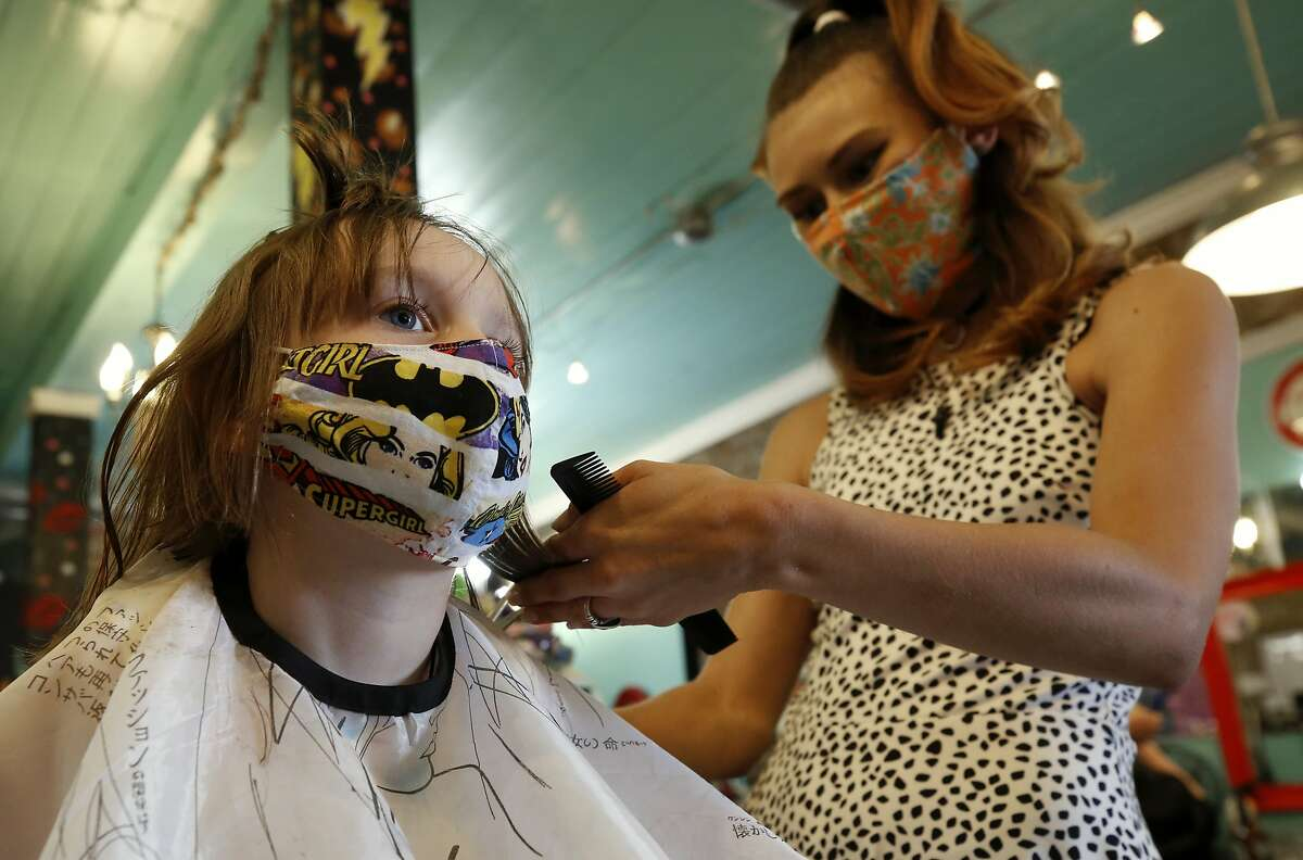 FILE - In this May 4, 2020, file photo, Robin Sotomayor, 5, wears a Supergirl face mask as she gets her hair done by Haylee Cummins at Rockabetty's Hair Parlor, in Yuba City, Calif. Donning a mask will be as common as putting on a cap or sunglasses for Californians as the state begins gradually easing stay-at-home orders, but rules about face coverings vary from county to county and it is unclear what enforcement might look like. (AP Photo/Rich Pedroncelli, File)