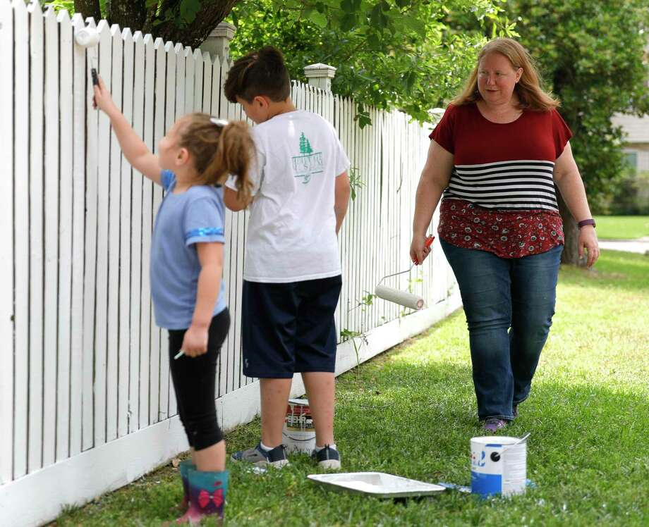 Sondra Hernandez, right, watches the work of her children Annie and Henry as they touch up their home's freshly painted fence, Friday, May 8, 2020, in Conroe. The Hernandez family made the fence painting into a daily project to keep the kids active and spend some quality time together outdoors. Photo: Jason Fochtman, Houston Chronicle / Staff Photographer / 2020 © Houston Chronicle