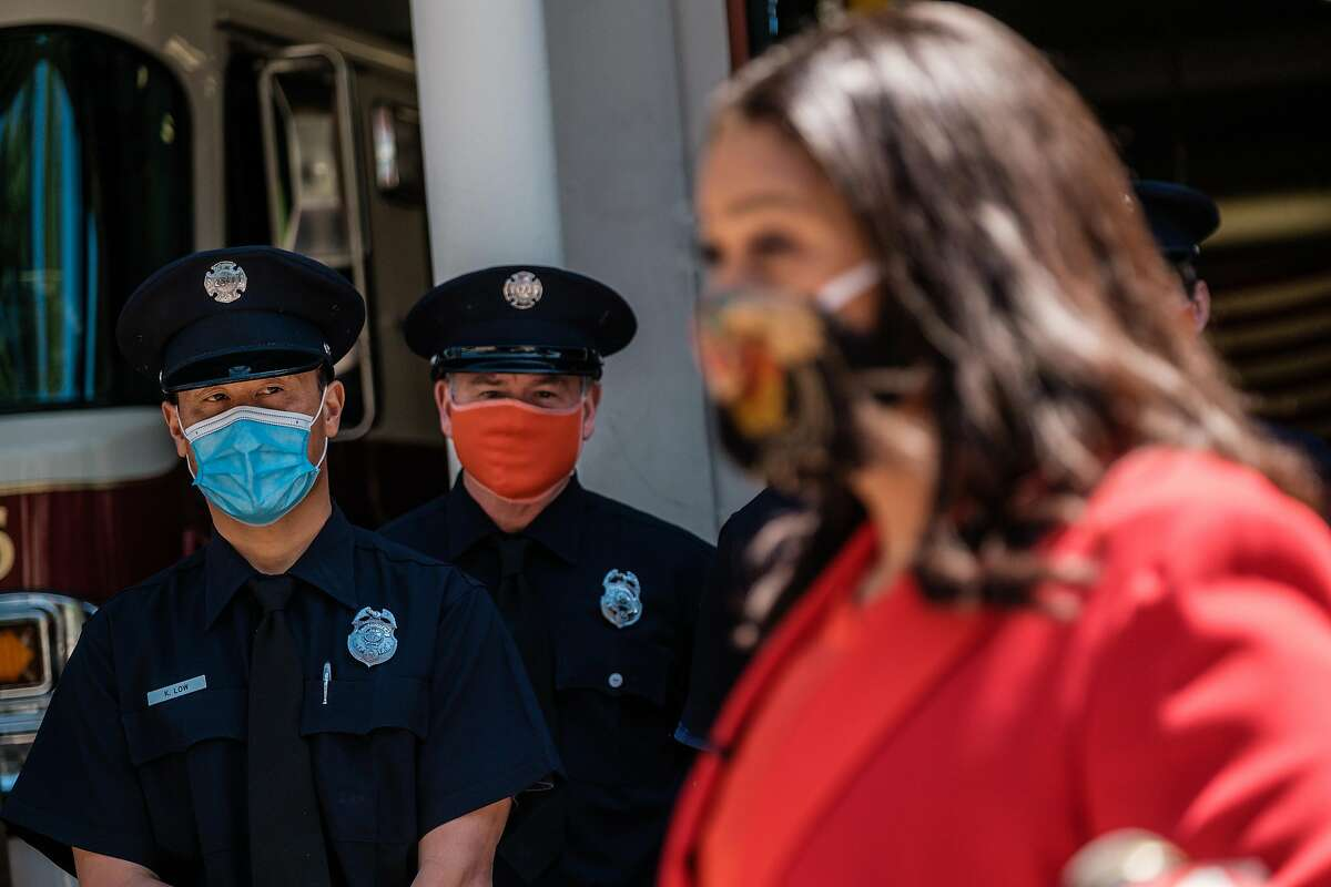 Firefighters and paramedics listen to Mayor London Breed at Fire Station 6 while she distributes meals from Z Zoul Sudanese Cafe as part of International Firefighters Day. in San Francisco, Calif. on Monday, May 4, 2020.