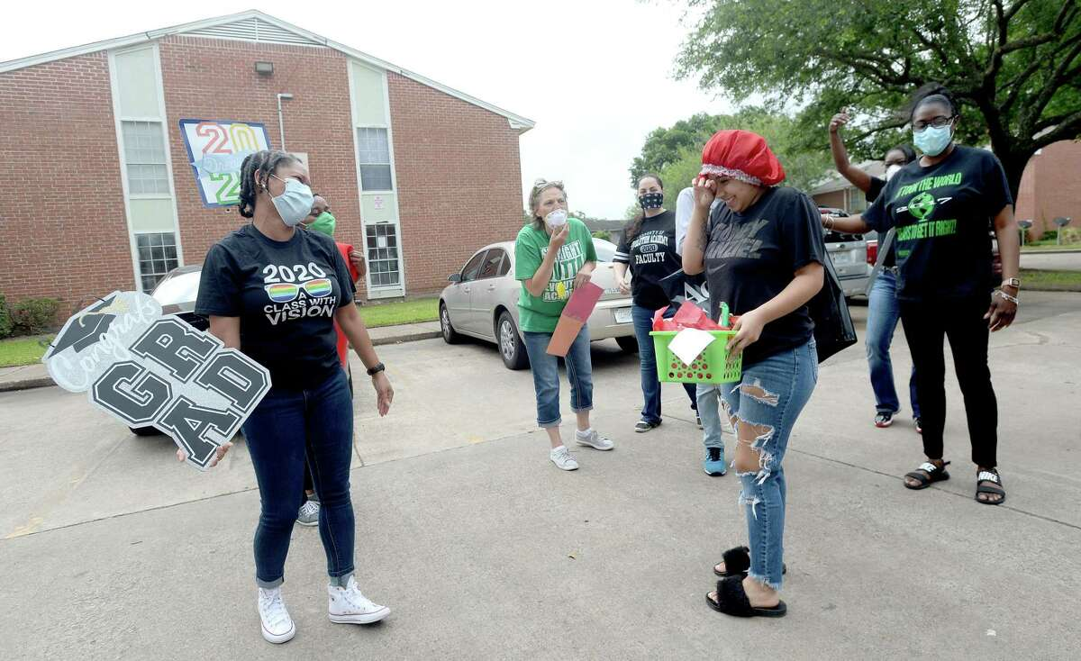 Evolution staff cheer and take photos with graduating seniors, including Kennedy Elliott, as they stop by each of their homes to drop off a basket of treats and celebrate them during what normally would be a senior picnic. Photo taken Friday, May 8, 2020 Kim Brent/The Enterprise