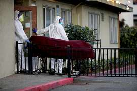 "Men donning hazmat suits bring a body out of Gateway Care and Rehabilitation, located at 26660 Patrick Ave., on Wednesday, April 8, 2020, in Hayward, Calif. Six residents at the skilled nursing home in Hayward have died after being infected by the coronavirus in an outbreak at the facility that has infected 29 other residents and 24 staff members.   Alameda County public health spokeswoman Neetu Balram confirmed the outbreak Wednesday afternoon.Officials are also monitoring an outbreak at East Bay Post-Acute Rehab in Castro Valley where seven people, including four staffers, have tested positive. Balram cautioned the number of infected persons at each facility could be updates and should be considered a ""point-in-time"" count. Health officials are tracing suspected and confirmed cases of COVID-19 at long-term care facilities throughout the county, Balram said."