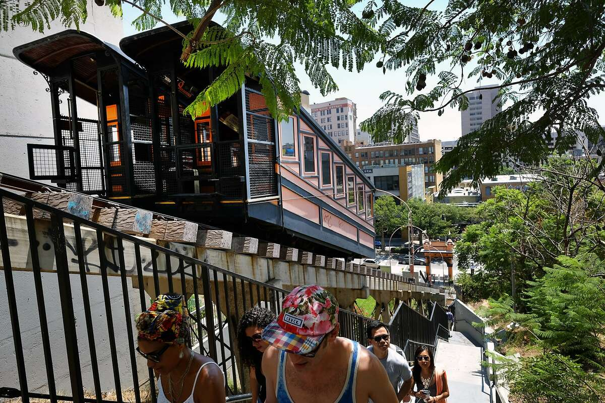 Pedestrians walk up a flight of stairs next to Angels Flight railway in downtown Los Angeles on Friday, July 24, 2015. The historic Angels Flight railway connecting two downtown Los Angeles districts is getting another look by transportation officials who have agreed to study possible ways for the now-shuttered trains to reopen. The Los Angeles County Metropolitan Transportation Authority board agreed at its meeting Thursday, July 23, 2015, to study the railway's safety record, even though it is regulated by the state utility commission, the Los Angeles Times reported. (AP Photo/Richard Vogel)