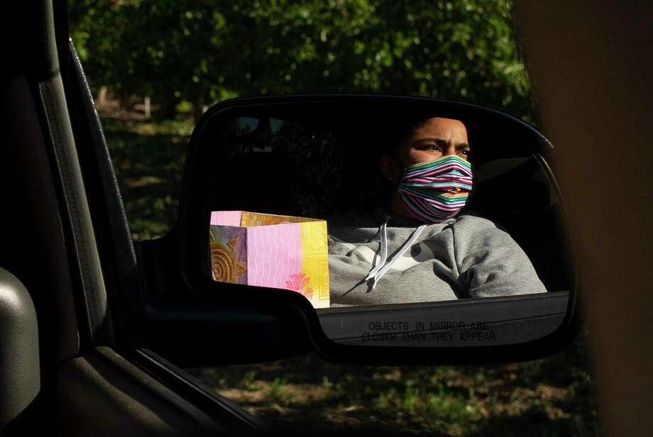 Washington State Labor Council union and naturalization organizer Dulce Gutiérrez holds a bag of donated cloth masks as she is reflected in a side view mirror while looking for farmworkers in an orchard Thursday, May 7, 2020, near Granger, Wash. (Evan Abell/Yakima Herald-Republic via AP) Photo: Evan Abell, AP / Yakima Herald-Republic