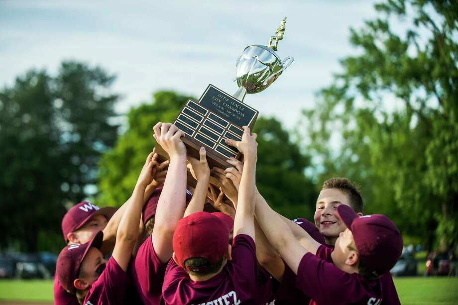 Members of the Wilson Miller Little League team hold the trophy aloft after winning the major city championship game on June 17, 2019. (Daily News file photo)