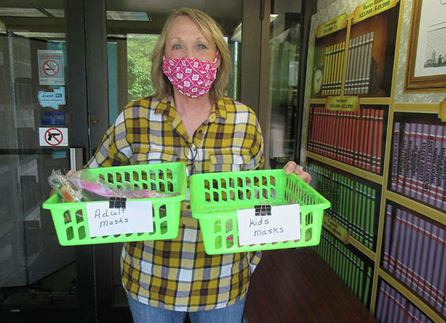 Anita Driver displays homemade face masks now available in the foyer of Jerseyville Public Library. The masks, made by Terry Woods, are available in the recently reopened free Little Library inside the building's entrance. Photo: Dylan Suttles | Hearst Illinois