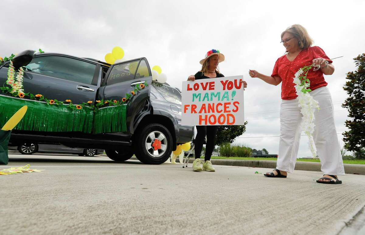 Sheila Atkinson, left, shows her sister, Susie Weissbach, the sign she made for their 90-year-old mother, Frances Hood, before a parade at Spring Creek Village Assisted Living & Memory Care, Friday, May 8, 2020, in Spring.