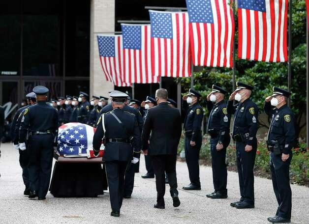 Houston Police officers salute as they lined up for the arrival of Houston Tactical Flight Officer Jason Knox's body from the funeral home during his funeral at Houston's First Baptist Church, in Houston, Saturday, May 9, 2020. Photo: Karen Warren, Houston Chronicle / Staff Photographer / © 2020 Houston Chronicle