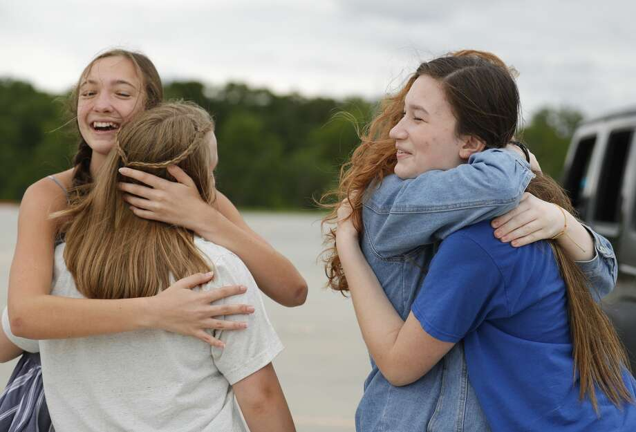 Tori Fruend, right, hugs Candice Clayburg as Lauren Francis embraces Ashton Hughes as the group of friends see each other in person for the first time in two months as seniors at Lake Creek High School picked up graduation appeal and yard signs, Friday, May 8, 2020, in Montgomery. Photo: Jason Fochtman/Staff Photographer / 2020 ? Houston Chronicle